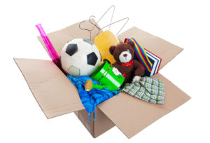 A box of unwanted stuff ready for a garage sale or to donate to a charitable organization.  Shot on white background.